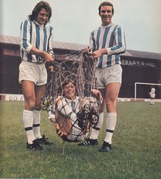 July 1971. Huddersfield Town pre-season photo shoot produced this bizarre effort where centre forward Frank Worthington and centre half Roy Ellam put one of the juniors, Steven Spraggs in the net.