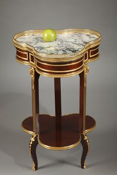 A late 19th century mahogany and mahogany veneer table with gilded and chiseled bronze decoration, provided with three compartments and a rotating Jura purple Brocatelle marble tray adorne