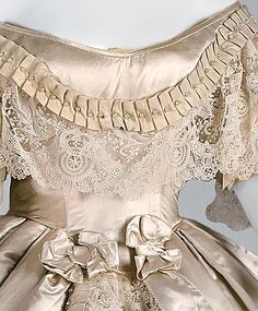 """Worth & Bobergh gown detail    Worth & Bobergh  Evening gown, 1861  Silk satin, silk ribbon, handmade """"Point de Gaze"""" lace    Charles Frederick Worth and Otto Bobergh founded Worth & Bobergh in Paris in the fall of 1857 or 1858. In 1860, the business appeared in the local trade directory under """"couturiers et nouveautés confectionnées"""" (designers and prepared novelties). By the 1870s, Bobergh was no longer involved with the company, and the House of Worth was well established as the arbiter…"""