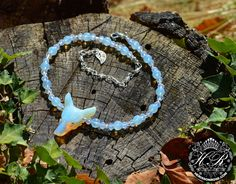 Opalite wolf necklace with carved wolf's head, opalite beads, opalised milky glass crystals and seed beads.OPALITE (also known as Sea Opal or opalised glass) is a man-made gemstone known for it's striking appearance - it fluoresces with a pale blu.