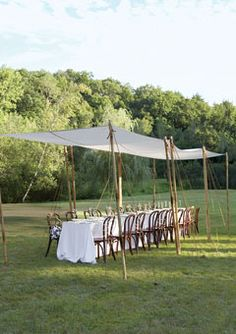 Brides.com: . Casual Dinning  Keep things cozy. The linear look of this long feasting table works nicely under an oblong tent. Bistro-style chairs (here, every other one was tied with ribbon) keep the look casual. Tables are draped in white cotton and topped with embossed-paper overlays; handcrafted plates complete the picture. Eight-foot canvas squares (available to rent) held up by bamboo poles provide both shade and style.  Canopies,   Kelly Scott Designs. Chairs, tablecloth, and…
