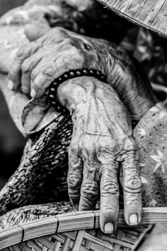 TRAVEL PORTRAITS - Years - An old vietnamese woman sitting by the side of the road in the middle of the food market in Hoi An, Vietnam. Her beautiful hands nicely illustrated her long life. Hoi An, Vietnam.