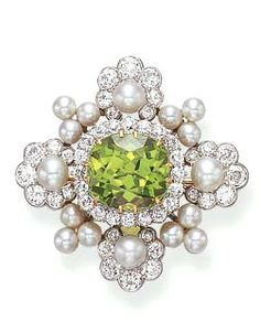 A DIAMOND, PEARL AND PERIDOT BROOCH, BY TIFFANY  CO.  Centering upon a cushion-cut peridot, within an old European-cut diamond surround, extending pearl and old European-cut diamond florets, spaced by pearl clusters, mounted in gold, circa 1880, in a Tiffany  Co. white leather case Signed Tiffany  Co., no. 9021 (indistinct)  The pearls have not been tested for natural origin