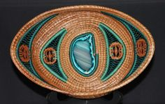 """Just finished this 12"""" x 8"""" pine needle basket with a stunning turquoise 3.5""""x2"""" agate centerpiece. It is accented by teal and turquoise stitching and embellished with black walnut slices."""