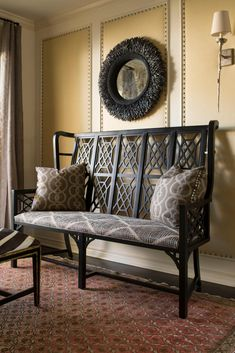 Texture, pattern and detail pack a powerful punch in this transitional foyer. A feathered mirror hangs above an upholstered bench with beautiful wrought iron detailing, and behind, nailhead trim outlines the sections of molding on the wall.