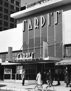 1937 exterior view of Sardi's Restaurant and Nite Club, with several people strolling by, and a bicycle at the curb. The building, located at 6313 Hollywood Boulevard, was redesigned in the 1930s by A.C. Balch and R.M. Schindler specifically for the restaurant.