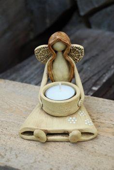 Keramický anděl sedící - svícen Keramický andílek ze šamotové hlíny, patinován burelem, dozdoben glazurou. Výška11,5 cm, délka od chodidel 11 cm. Ručně modelován.