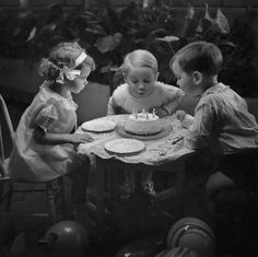 Three children blowing out candles on birthday cake circa 1934