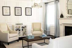 elegant and airy.   love the mirrored cabinet, neutral palette, and trim detail.