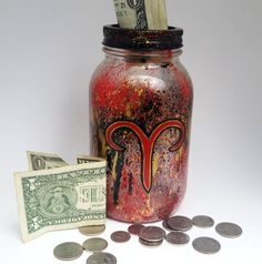 Want a cool way to save money and to show off your zodiac sign? Then this mason jar bank is perfect!  Pictured is the Aries symbol, the ram, painted on the outside of the jar. The same colors are splattered on the inside of the jar, giving it depth and character. Aries is one of the first signs of the zodiacs, being March 21- April 19. The signs colors are red, black, and gold.  This makes an awesome and unique gift to the horoscope lover in your life, even if its just for you! Its an…
