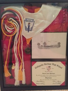 Graduation shadow box with graduation gown, cap, diploma, cords, stole, and medals