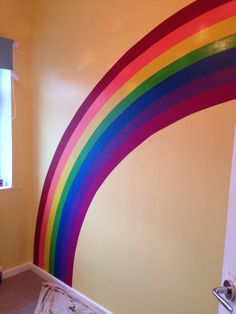 Rainbow painted on wall for nursery. Used paint tester pots and lots of 'frog tape' masking tape.