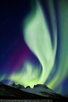 Northern lights over Mt Snowden Aurora borealis swirls across the sky over the Brooks mountain range, Snowden mountain, arctic Alaska.