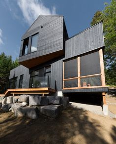 Two volumes are stacked at irregular angles to form this Canadian forest retreat, which Montreal-based architecture firm Atelier Boom-Town designed for siblings.
