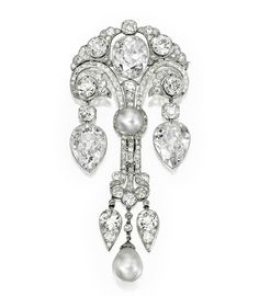 MAGNIFICENT PLATINUM, NATURAL PEARL AND DIAMOND CORSAGE ORNAMENT, CIRCA 1910.  Centered by a button-shaped natural pearl measuring 10.79 by 10.63 mm, surmounted by a cushion-cut diamond weighing 8.67 carats and flanked by two pear-shaped diamond drops weighing 9.59 carats and 8.78 carats, completed by a natural pearl drop measuring 11.88 by 11.69 mm, accented throughout by numerous old European, old mine and rose-cut diamonds weighing approximately 19.50 carats, length approximately 4…