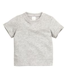 CONSCIOUS. Een sweater van gewassen joggingstof van biologisch katoen. De sweater heeft korte mouwen met een vastgestikte omslag onderaan, een drukknoop op één van de schouders en een boord aan de onderkant.