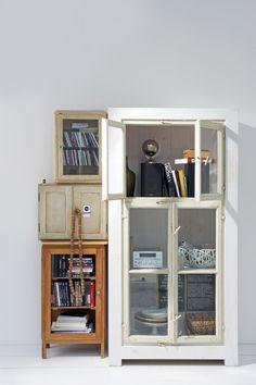 Een verzameling oude kasten in verschillende maten is een leuke plek om je geluidsinstallatie en cd's in op te bergen. Verschillende maten kasten gestapeld.