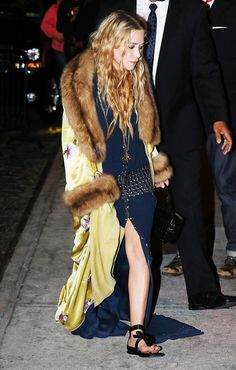Mary-Kate Olsen wears a blue maxi dress with a floral yellow coat with fur detailing and flat bow sandals