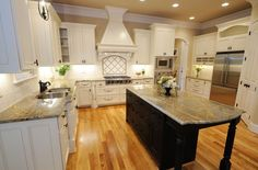 A traditional kitchen with white cabinetry and a contrasting black center island. The hardwood floors are in a warm honey oak.