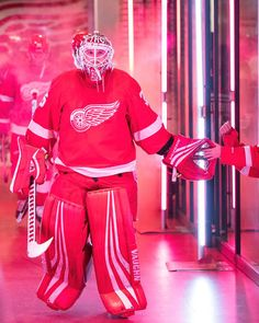 DETROIT, MI - OCTOBER 26: Goaltender Jimmy Howard #35 of the Detroit Red Wings pounds gloves with a fan on his way to the ice prior to an NHL game against the Winnipeg Jets at Little Caesars Arena on October 26, 2018 in Detroit, Michigan. (Photo by Dave Reginek/NHLI via Getty Images)