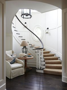 This sweeping staircase is gorgeous. A cozy vignette at the foot of the stairs is inviting. - Traditional Home ® / Photo: Colleen Duffley / Design: Tammy Connor Foyer Staircase, Curved Staircase, Staircase Design, Stairs, Staircase Handrail, Staircase Ideas, Winding Stair, Traditional House, Traditional Design