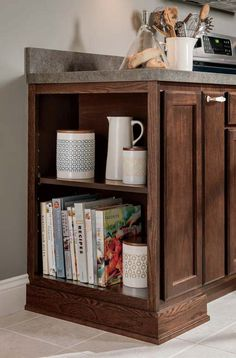 Achieve a well-curated open shelf look by keeping cookbooks and serveware within reach on Aristokraft's Oakland base cabinet shelves in an Umber finish on oak.