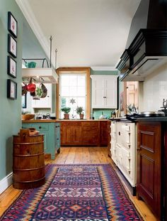 Hanging pots and pans, rug, big stove, and a window over the sink
