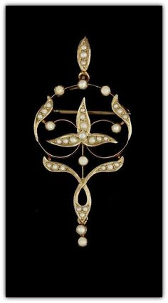 Art Nouveau 9 ct. gold pendant and chain with a delicate openwork design, decorated with seed pearls of varying sizes.