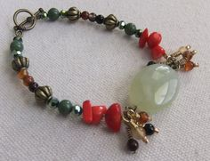 A large green quartz oval is flanked by brass and red agate charms. Coral nuggets, brass beads, green crystals, green aventurine, and additional