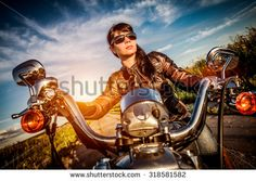 Biker girl in a leather jacket on a motorcycle looking at the sunset. Filter applied in post-production. - stock photo