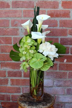 Splendid arrangement with orchids, lilies and roses in a glass vase.