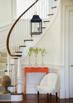 white entry. black lantern. orange table.