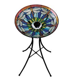 "Solar Birdbath And Stand Set HA5215 In Stock! $69.95 • Glow-in-the-dark Dragonfly Glass Birdbath And Metal Stand • Tiffany-inspired glass is easy to rinse off and will not rust • Center solar panels absorb the sun's energy by day to release a soft glow at night • Use as a traditional birdbath or fill with birdseed Size 17-1/2""L x 3-3/4""W x 17-1/2""H"