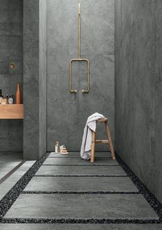 a grey concrete bathroom with pavement tiles and gravel on the floor plus gold fixtures to add chic to the space - DigsDigs Grey Bathrooms Designs, Bathroom Interior Design, White Bathrooms, Luxury Bathrooms, Master Bathrooms, Dream Bathrooms, Industrial Bathroom Design, Cement Bathroom, Modern Bathroom