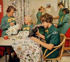 Late 1950s or very early 1960s Girl Scout Troop making curtains for meeting room with the assistance of a Senior Girl Scout and their Troop Leader.
