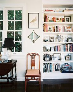 Clean white walls + bookcases on bookcases on bookcases