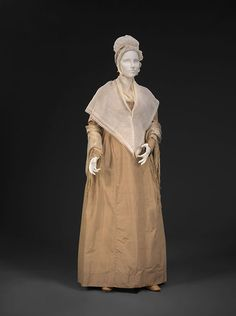 "Quaker Dress, 1800-1805, tan silk. In the early 1800s, Quaker dresses still kept up with contemporary fashion. The raised waistline, elongated sleeves, and  drawstring neckline of this dress echo popular styles at the time. ""Dressing Plain"" (trims other than piping and pleats were frowned upon) meant subdued solid colors, like grays, tans, pale golds, and olive greens. There was no prohibition of costly fabrics, so Quaker dresses often use  high-quality silk taffetas and  satins."