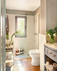 Baño pequeño en blanco y gris. La ducha al fondo