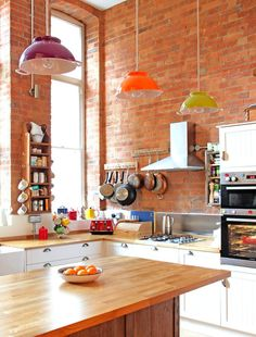 I love so much about this kitchen: the exposed brick, convenient pot racks, wall ovens, warm wood counters, lots of light from the windows, quirky colander light fixtures, and bright pops of color.