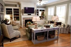 The family room is done in sage greens while the back of the shelves are painted darker