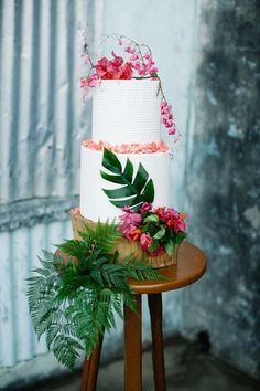 Jungle Wedding Cake: Pick a simple cake and decorate it with pink florals and ferns included in your jungle wedding theme.