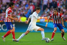 Gareth Bale breaks with the ball under the watchful eye of Tiago and Filipe Luis during the UEFA Champions League final match between Real Madrid CF and Club Atlético de Madrid at Estadio Da Luz on May 24, 2014 in Lisbon, Portugal.