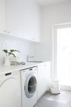 Modern white laundry room features white cabinets paired with white countertops and a white grid tiled backsplash. Modern white laundry room features white cabinets paired with white countertops and a white grid tiled backsplash. Laundry Nook, Laundry Room Layouts, Laundry Room Organization, Laundry Storage, Small Laundry, Laundry In Bathroom, Garage Laundry, Laundry Decor, Laundry Closet