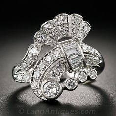 This singular and sensational cocktail, or dinner, ring (or both), is handcrafted in platinum and hails from the 1940s-50s. The free swingin' design incorporates classic scroll and fan motifs with artsy, free-form, Deco/Retro flair. 1.40 carts of high-color European-cut, baguette and single-cut diamonds pack some serious sparkle