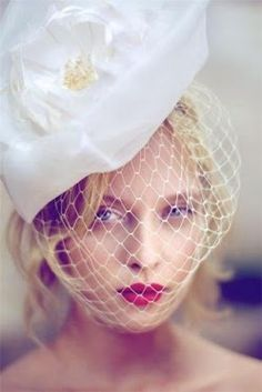 Will you be wearing a veil on your big day? We love the way her pink lipstick pops behind her netted veil.