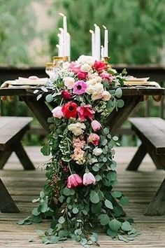 Greenery table runner with pink flowers for rustic wedding.