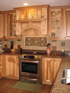 Natural Beautiy - Guests often enter this kitchen to the smells of homemade bread, making it an inviting place to visit. Set in the picturesque countryside, this natural hickory kitchen truly blends with its environment. Inspired by the client's appreciation of nature, the physical characteristics found in the hickory cabinetry set the tone.  Mullion door cabinets and plate ledges provide display areas for pottery, heirlooms and other collectibles. Lighting, tile and countertop selections...