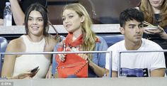 Three's a crowd: The reality star, the 20-year-old model and 26-year-old musician sat together at the match
