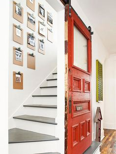 In the hallway, a cherry-colored salvaged door glides along barn door hardware, sliding open to gray-and-white-painted stairs that climb to . Doors, Renovations, Exterior Doors, Vintage Cottage, Remodel, Salvaged Door, Diy Staircase, Old Cottage, Cottage Renovation