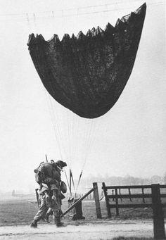 A paratrooper helping a fallen buddy.